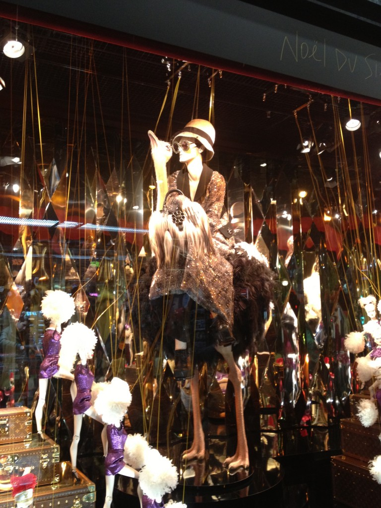 An impeccably stylish mannequin riding a rotating Ostrich